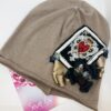 cappello in cotone chiaro con applicazione a forma di carta da gioco e fiocco in raso con pietre